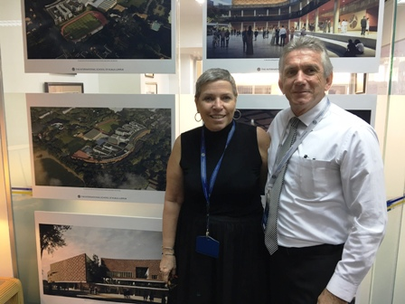 Head of School Norma Hudson and Senior Associate Ray Sparks stand in front of photos of the new campus